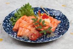 三文鱼生鱼片服务用石灰调味汁、土豆沙拉和ikura服务在washi日文报纸的气喘的墨水板材 库存照片
