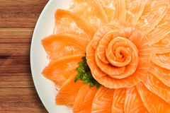 三文鱼生鱼片服务顶视图在花形状的在木桌背景,日本式的白色冰碗小船 库存图片
