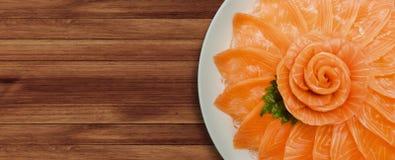 三文鱼生鱼片服务顶视图在花形状的在木桌背景,日本式的白色冰碗小船 免版税库存照片