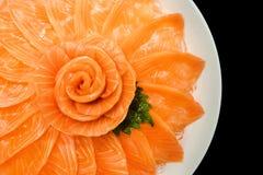 三文鱼生鱼片服务顶视图在花形状的在黑背景隔绝的白色冰碗小船,日本式 库存照片