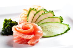 三文鱼生鱼片用在白色背景的黄瓜 免版税库存图片