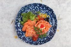三文鱼生鱼片顶视图服务用石灰调味汁、土豆沙拉和ikura服务在washi日文报纸的气喘的墨水板材 库存照片