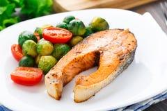 三文鱼用烤抱子甘蓝和蕃茄 库存图片