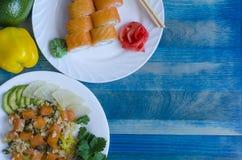 三文鱼用米和鲕梨在一个白色板材和寿司在蓝色捅背景 库存图片