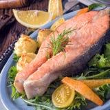 三文鱼用黄油油煎了土豆汤和沙拉 免版税库存照片