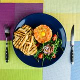 三文鱼鞑靼服务用蕃茄、葱和油煎方型小面包片在稀土 免版税库存照片