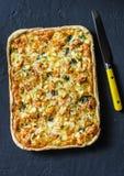 三文鱼,韭葱,菠菜,乳酪在黑暗的背景的油酥点心饼 库存图片