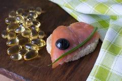 三文鱼,鱼肝油药片 图库摄影