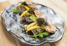 三文鱼Soba用面条、草本和海草在黑盛肉盘 库存图片