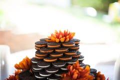 三明治曲奇饼与橙色花的婚宴喜饼 图库摄影