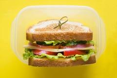 三明治用乳酪、火腿和新鲜蔬菜在一个容器在黄色明亮的背景 库存图片