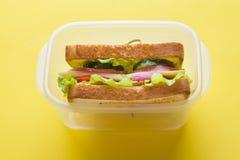 三明治用乳酪、火腿和新鲜蔬菜在一个容器在黄色明亮的背景 免版税库存照片