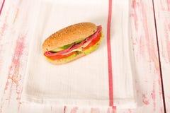 三明治用乳酪、蕃茄、蒜味咸腊肠、黄瓜和莴苣在wo 免版税库存照片