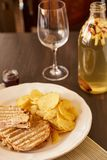 三明治用乳酪和香肠在格栅油煎了 有芯片和多士面包快餐的一块板材  白色盘用的开胃菜 库存照片