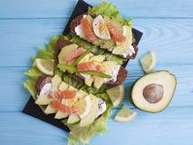 三明治用土气鲕梨红色鱼午餐柠檬蓝色木的开胃菜 免版税库存照片