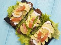 三明治用土气鲕梨红色鱼午餐柠檬食家蓝色木的开胃菜 库存图片