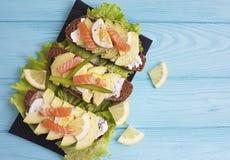 三明治用土气鲕梨红色鱼午餐蓝色木的开胃菜 免版税库存图片