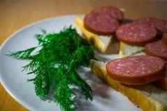 三明治用在一块白色板材的肉香肠,装饰用莳萝-茴香 库存图片