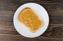 三明治用在白色板材的花生酱在黑暗的桌上 库存照片