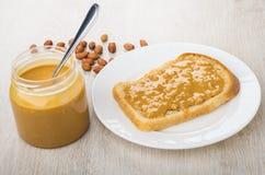 三明治用在白色板材,瓶子的花生酱用黄油 库存图片