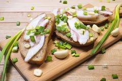 三明治用烟肉和葱用大蒜在一个木切板 免版税库存图片