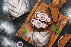 三明治用盐味的鲱鱼、葱和黑麦面包在切板 顶视图 免版税库存图片