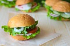 三明治用蕃茄莴苣和火腿和葱在一张木桌上 图库摄影