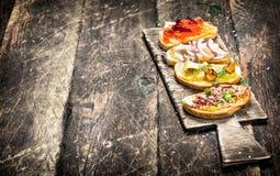 三明治用蘑菇、蒜味咸腊肠、红色鱼子酱和新鲜蔬菜在敬酒的面包 图库摄影