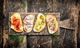 三明治用蘑菇、蒜味咸腊肠、红色鱼子酱和新鲜蔬菜在敬酒的面包 库存图片