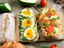 三明治用鲕梨、鸡蛋和蕃茄在木背景 免版税图库摄影