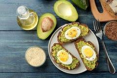 三明治用鲕梨纯汁浓汤和鸡蛋在一块板材和成份烹调的在一张蓝色木桌上 在视图之上 免版税库存图片