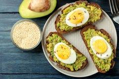 三明治用鲕梨纯汁浓汤和鸡蛋在一块板材和成份烹调的在一张蓝色木桌上 在视图之上 免版税图库摄影