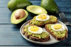 三明治用鲕梨纯汁浓汤和鸡蛋在一块板材和成份烹调的在一张蓝色木桌上 免版税库存照片