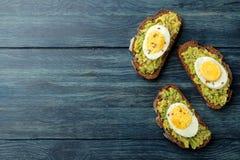 三明治用鲕梨纯汁浓汤和鸡蛋在一张蓝色木桌上与空间文本的 在视图之上 库存图片