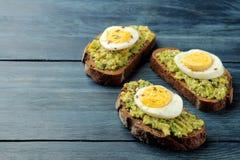 三明治用鲕梨纯汁浓汤和鸡蛋在一张蓝色木桌上与空间文本的 库存图片