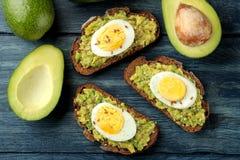 三明治用鲕梨纯汁浓汤和鸡蛋在一张蓝色木桌上 在视图之上 免版税库存照片