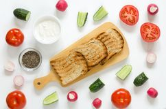 三明治的成份:乳脂干酪,新鲜的黄瓜,萝卜,蕃茄,在白色背景的chia种子 免版税库存图片