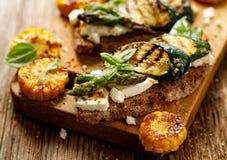 三明治素食主义者 全麦面包三明治用希腊白软干酪、烤夏南瓜、绿色芦笋、糖豌豆,橄榄油和她 免版税库存照片