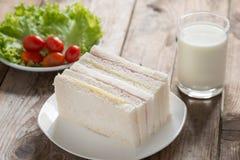 三明治、火腿用乳酪和牛奶在木桌上 免版税库存照片