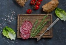 三明治、面包、蕃茄、香肠和葡萄酒刀子的成份在木板和黑暗的背景,顶视图 免版税库存图片