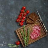 三明治、面包、蕃茄、香肠和葡萄酒刀子的成份在木板和黑暗的背景,顶视图 免版税库存照片