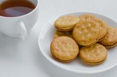 三明治奶油色薄脆饼干用热的茶 库存照片