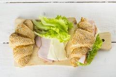 三明治新月形面包的成份用莴苣,烟肉,在白色木背景的乳酪 免版税库存图片