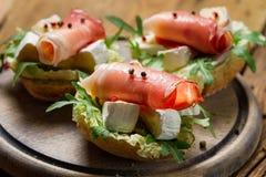 三明治特写镜头用帕尔马火腿,咸味干乳酪乳酪和火箭婆罗双树 免版税库存照片