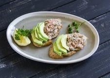 三明治用在一块卵形板材的鲕梨、三文鱼和全麦面包黑暗的木表面上 库存图片