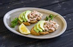 三明治用在一块卵形板材的鲕梨、三文鱼和全麦面包黑暗的木表面上 免版税库存图片