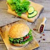 三明治用油煎的豆炸肉排、新鲜的莴苣、红辣椒和黄瓜 鲜美三明治和成份在老木背景 库存图片