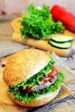 三明治用油煎的豆炸肉排、绿色莴苣、红辣椒和黄瓜 可口三明治和成份在一个木板 免版税库存图片