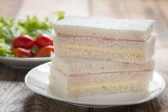 三明治用火腿和乳酪在白色板材 免版税库存图片
