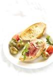 三明治用火腿和橄榄在一块白色板材 免版税库存图片